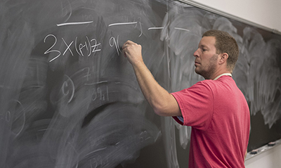 Faculty writing on chalkboard